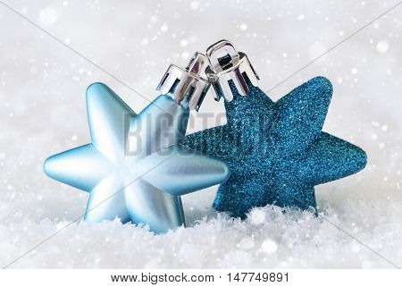 Dark And Light Blue Christmas Tree Balls With Star Shape. Macro Or Close Up View. Christmas Decoration Or Ornament On Snow With Snowflakes. Christmas Greeting Card For Seasons Greetings