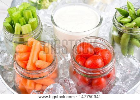 Canning jars full of fresh vegetables with ranch dip in an ice bucket for a healthy picnic snack. Closeup in horizontal format.
