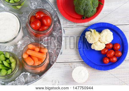 Healthy picnic snacks in canning jars on a rustic wood picnic table. Vegetables jars in metal ice bucket seen form a high angle.