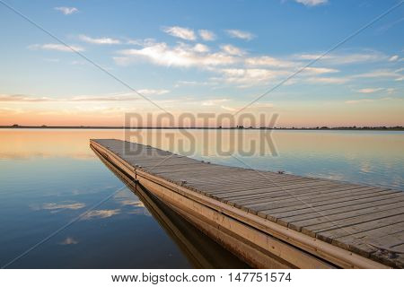 A fishing pier on a Colorado lake in larimer County at sunrise