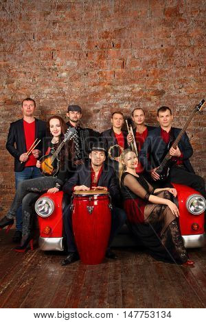 Brass band of eight people in red and black clothes pose in studio with car sofa
