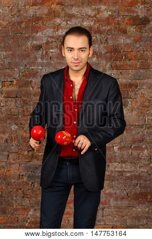 Handsome man in suit stands with red maracas in studio with brick wall