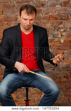 Man in black jacket plays sticks in studio with red brick wall
