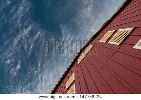 Deep Blue Sky Above Angle View of Barn Wall with yellow gables