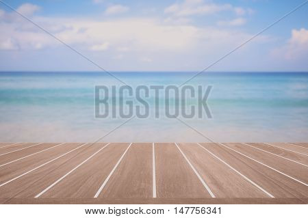 Brown wood floor and abstract blurred background of blue sea and sky