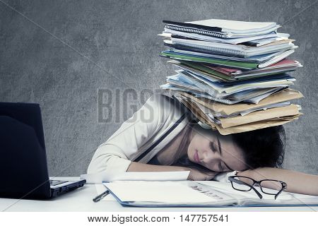 Photo of a depressed female worker sleeping on the table with a pile of paperwork on her head