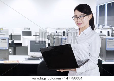 Beautiful female employee holding a laptop while standing in the office room and smiling at the camera