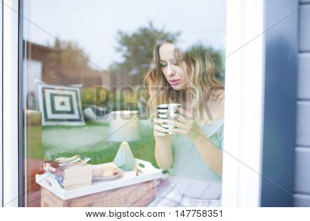 Young beautiful blonde woman with cup of coffee sitting home by the window. Backyard reflection on the glass. Lazy day off concept.