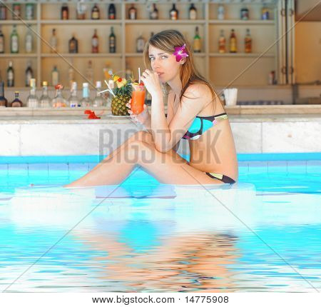 Girl in tropical pool bar with cocktail. Reflection in water.