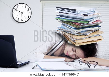 Photo of an overworked businesswoman sleeping on desk with paperwork on her head shot in the office