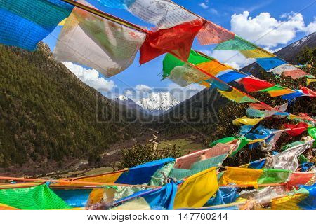 Snow mountain in China Southwestern in Sertar County of Garze Tibetan Autonomous Prefecture in Tibet Kham China with blurred prayer flags in foreground.