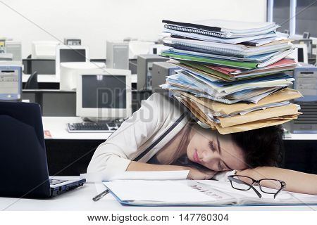 Image of a tired female entrepreneur sleeping on the table with laptop and paperwork on desk shot in the office