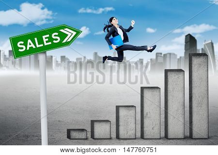 Growing sales concept. Asian businesswoman carrying document and jumping above chart with sales text on the signpost