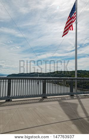 Vertical view on the Walkway Over the Hudson with a flag near the midway point.