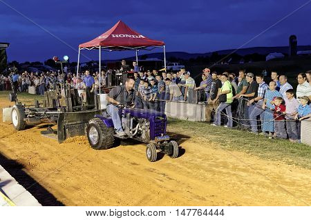 MYERSTOWN, PENNSYLVANIA - SEPTEMBER 16, 2016: A man drives a modified lawn tractor at Myerstown East End Days. The tractor pull is an annual community event.
