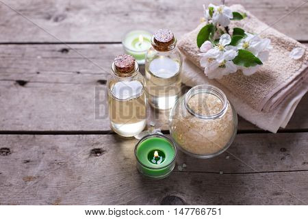 Spa. Sea salt towels aroma oil in bottles and flowers on vintage wooden background. Selective focus. Still life.