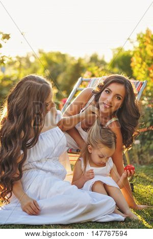 Three sisters. Two older sisters look after the youngest in the garden. Little girl eats a tomato. Family time. Human relationships. Setting sun. Fun.