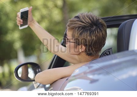 young Chinese woman taking photo in a convertible car