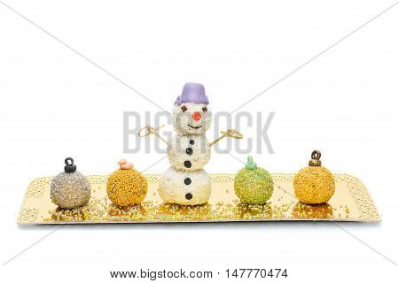 Sweet pops dessert with sprinkles made in shape of christmas balls and snowman on golden plate. Isolated over white background. Copy space.
