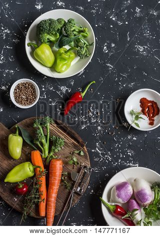 Fresh raw vegetables - carrots peppers broccoli turnips spices and herbs on dark background top view. Cooking ingredients