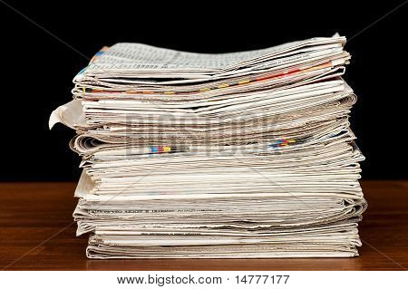 Heap Of Newspaper On A Wooden Table