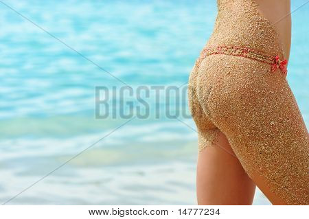 Woman on a beach in bikini with a sandy back
