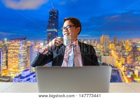 Asian businessman relaxing with cup of coffee and sitting at desk in front of blurred bangkok city background