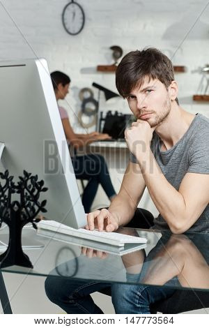 Young man working with computer, sitting at desk, looking at camera.
