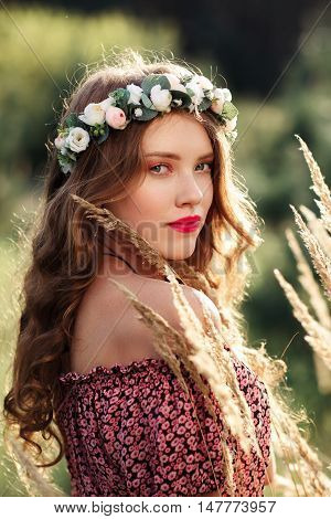 Beautiful girl in wreath standing near spikelets. Natural beauty, youth, freshness, summer concept