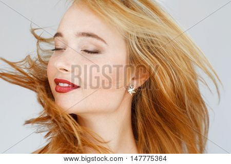 Close-up portrait of happy carroty woman with closed eyes. Adorable sunny girl feeling bliss, happiness, satisfaction