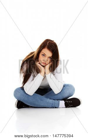 Young sad woman sitting on the floor