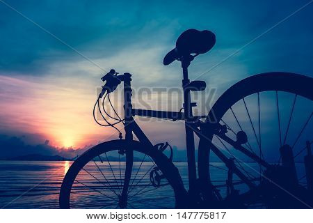 Silhouette of bicycle on the beach against colorful sunset in the sea blue sky background. Outdoors. Cross process and vintage tone effect.