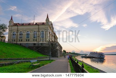 RYBINSK RUSSIA - JULY 21 2016: Unidentified people are walking on Volzhskaya quay near building of former Grain Exchange at sunset. On the river quay - cruise ship