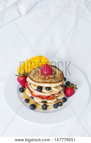Hotcakes with fruit in bed