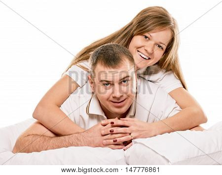 Happy smiling couple laying laughing in bed on white background
