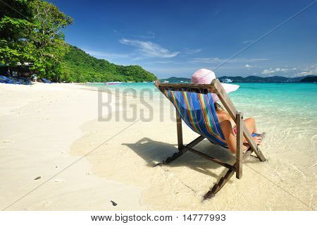Girl on a tropical beach in chaise lounge