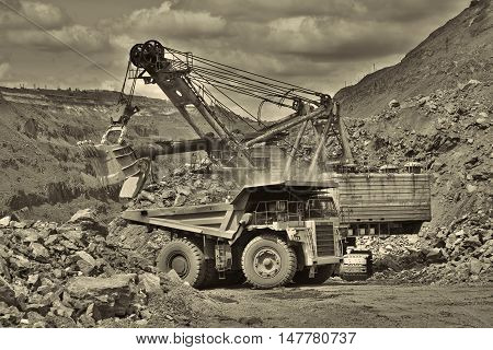 Excavator developing the iron ore on the opencast and loading it to the dump truck - black and white image