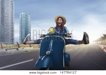 Beautiful happy asian woman riding a scooter raising both legs on the country road