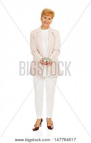 Smile elderly woman holding house model