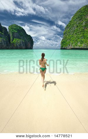 Woman running in water in beautiful lagoon at  Phi Phi Ley island, the exact place where