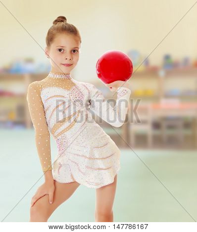 Against the background of a child's room .Beautiful little girl gymnast in elegant dress, posing with a red ball.