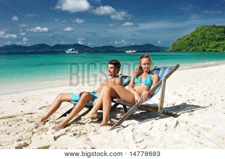 Paar an einem tropischen Strand in Chaise lounge