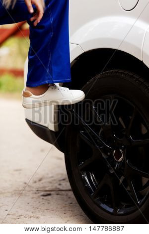 Woman is changing tire of car with wheel wrench