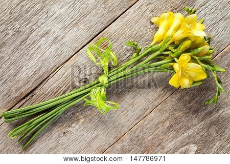 Bouquet of yellow freesias on old wooden surface
