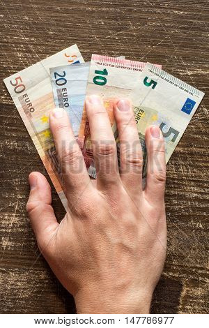 Hand is taking Euros. Concept for bribery or fraud.