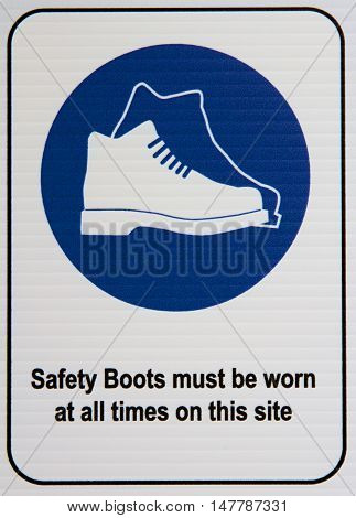 Safety boot signage at a construction site.
