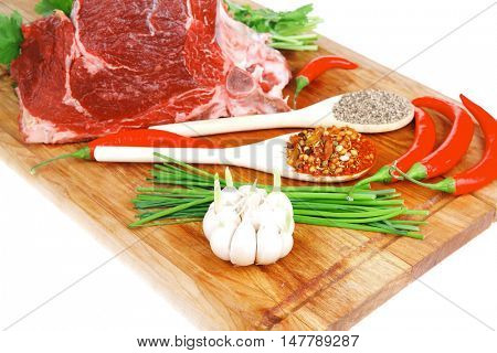 uncooked meat : raw fresh beef pork rib ready to cooking with garlic and red hot pepper over wood isolated over white background