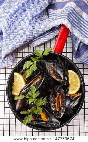 boiled mussels with lemon and parsley in an red and black enamel pot on cooling rack