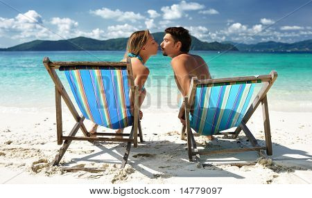 Couple kissing on a tropical beach in chaise lounge