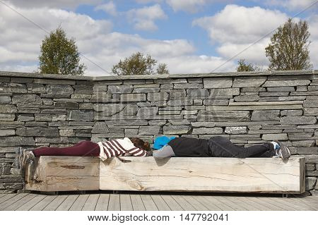 Norway travel picnic area. People resting. Stone wall. Travel background